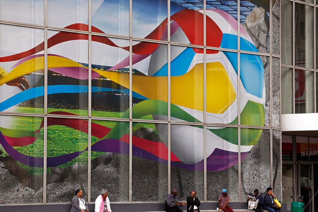 . People sit in front of a large advertising poster of a soccer ball,  by a food company promoting goods under the banner of the 2014 World Cup played in Brazil, in the city of Cape Town, South Africa, Wednesday, June 25, 2014.  Thousands of tourists visited South Africa during the 2010 World Cup with the City of Cape Town playing host to games. (AP Photo/Schalk van Zuydam)