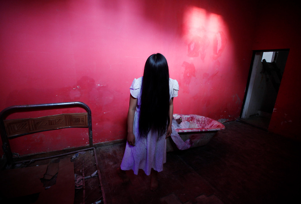 . Lineth Mollo portrays Samara Morgan, the central character of \'The Ring\' horror film, poses before performing at a House of Terror during a Halloween night in El Alto, Bolivia, Wednesday, Oct. 30, 2013. Bolivians from La Paz and El Alto, mostly of Aymara descent, have started to embrace Halloween celebrations introducing characters adapted from their own culture such as the bloodthirsty Cholita. (AP Photo/Juan Karita)