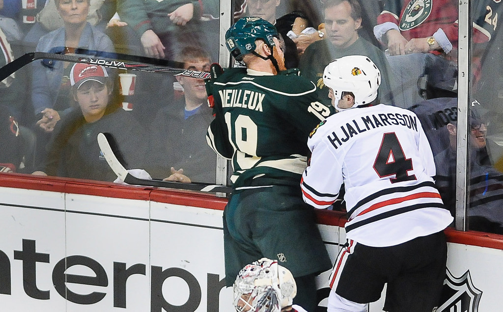 . Minnesota\'s Stephane Veilleuz slams head-first into the boards as he misses a check on Chicago defenseman Niklas Hjalmarsson in the second period  (Pioneer Press: Ben Garvin)