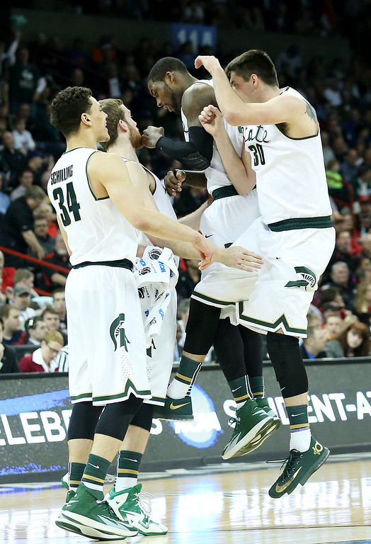 . SPOKANE, WA - MARCH 22:  The Michigan State Spartans celebrate in the first half against the Harvard Crimson during the Third Round of the 2014 NCAA Basketball Tournament at Spokane Veterans Memorial Arena on March 22, 2014 in Spokane, Washington.  (Photo by Stephen Dunn/Getty Images)