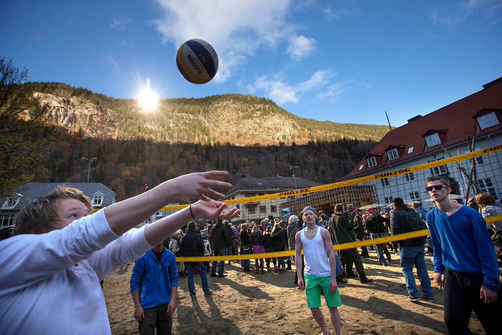 . A group of youths play games after the official opening of giant sun mirrors in the town of Rjukan, Norway, Wednesday, Oct. 30, 2013. Residents of the small Norwegian town of Rjukan have finally seen the light. Tucked in between steep mountains, the town is normally shrouded in shadow for almost six months a year. But on Wednesday faint rays from the winter sun for the first time reached the market square thanks to three 183-square-foot (17-square-meter) mirrors placed on a mountain. (AP Photo/NTB Scanpix, Terje Bendiksby)