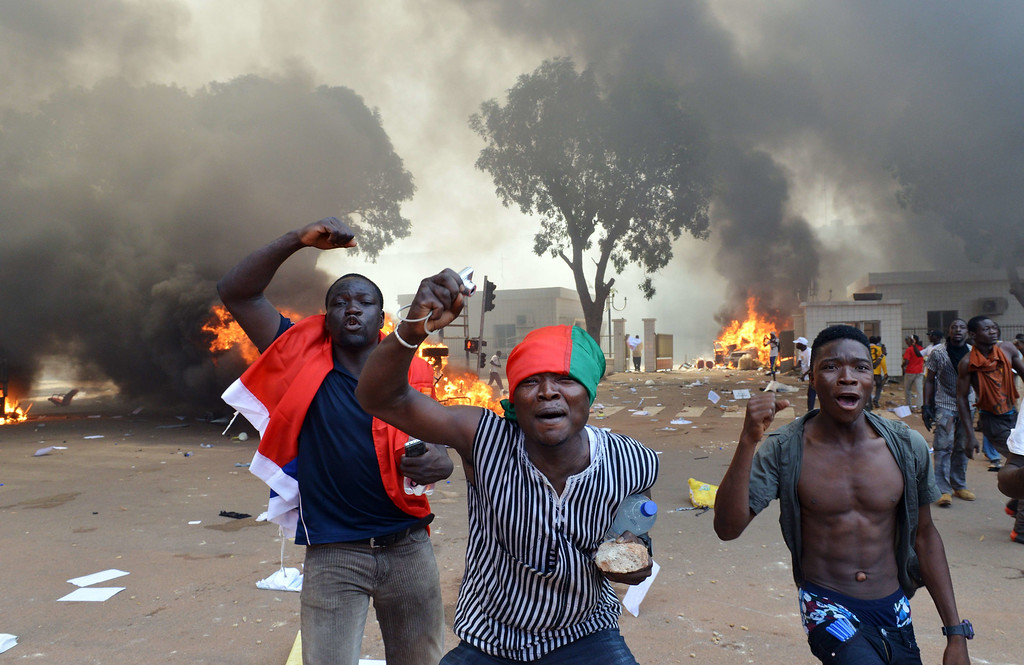 . Men shout slogans in front of burning cars, near the Burkina Faso\'s Parliament where demonstrators set fire, on October 30, 2014 in Ouagadougou, as they protest against plans to change the constitution to allow President Blaise Compaore to extend his 27-year rule.  ISSOUF SANOGO/AFP/Getty Images