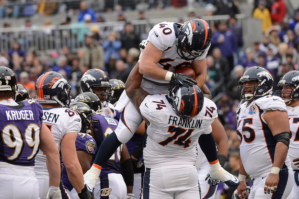 Description of . Denver Broncos running back Jacob Hester #40 is lifted by Denver Broncos tackle Orlando Franklin #74 after he scored the first touchdown of the game at the M&T Bank Stadium, in Baltimore, MD Sunday December 16, 2012.      Joe Amon, The Denver Post