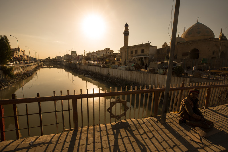 A man sitting on a bridge over a dirty and polluted canal in the city of Basra, Southern Iraq.