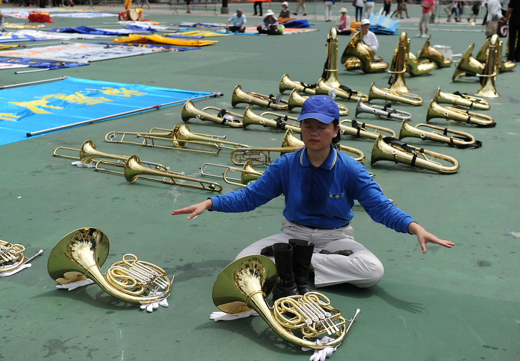 ". A member of a Falun Dafa band relaxes before a pro-democracy rally seeking greater democracy in Hong Kong on July 1, 2014 as frustration grows over the influence of Beijing on the city. July 1 is traditionally a day of protest in Hong Kong and also marks the anniversary of the handover from Britain to China in 1997, under a ""one country, two systems\"" agreement.   DALE de la REY/AFP/Getty Images"