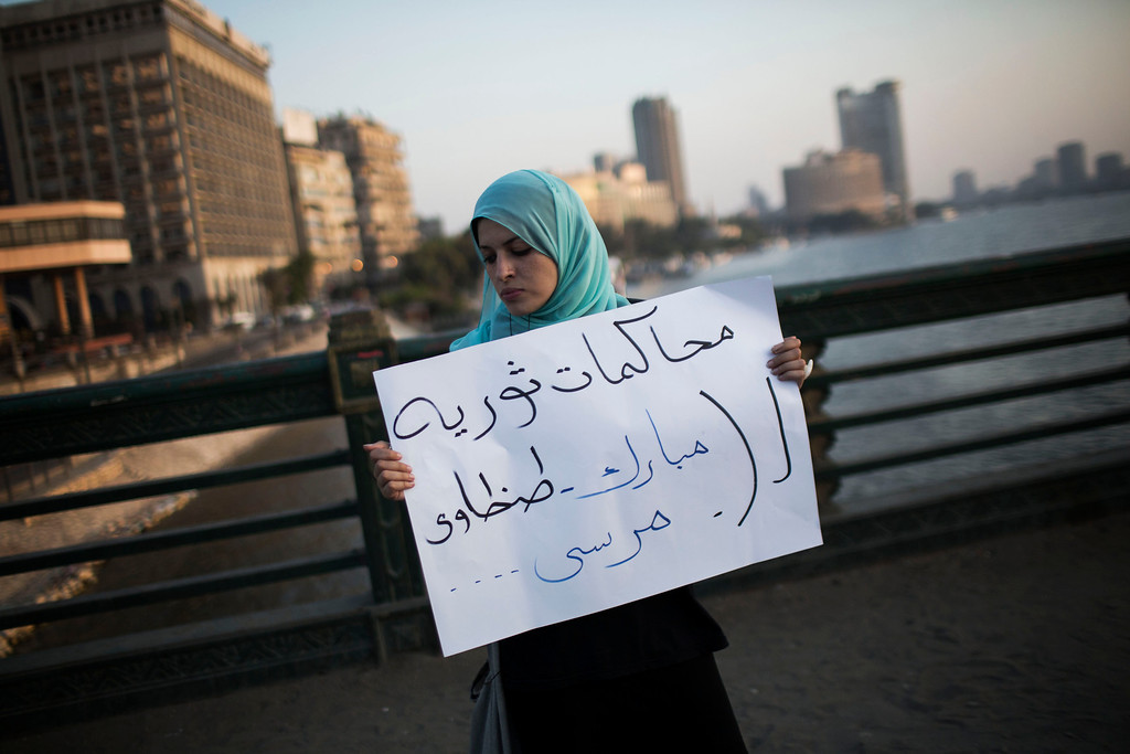 ". An Egyptian woman holds a banner that reads in Arabic ""Revolutionary trial for Mubarak, Tantaui and Morsi during a protest against the release of former Egypt\'s dictator Hosni Mubarak in Qasr Al-Nil bridge in downtown Cairo, Egypt, Thursday, Aug. 22, 2013. (AP Photo/Manu Brabo)"