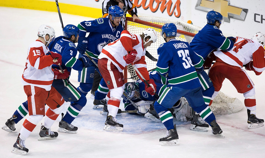 . Vancouver Canucks goalie Ryan Miller, bottom center, covers up the puck as teammates Kevin Bieksa (3), Henrik Sedin, of Sweden, (33), Jannik Hansen, of Denmark, (36) and Luca Sbisa, of Switzerland, defend against the Detroit Red Wings\' Riley Sheahan (15), Stephen Weiss (90) and Gustav Nyquist, of Sweden, (14) during the third period of an NHL hockey game in Vancouver, British Columbia on Saturday, Jan. 3, 2015. (AP Photo/The Canadian Press, Darryl Dyck)