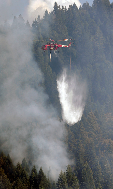 . A Skycrane helicopter drops its load of water on the King Fire near Pollack Pines, Calif., Monday, Sept. 15, 2014. The fire, which started Sunday has consumed more than 3,000 acres and forced the evacuation of dozens of homes.(AP Photo/Rich Pedroncelli)