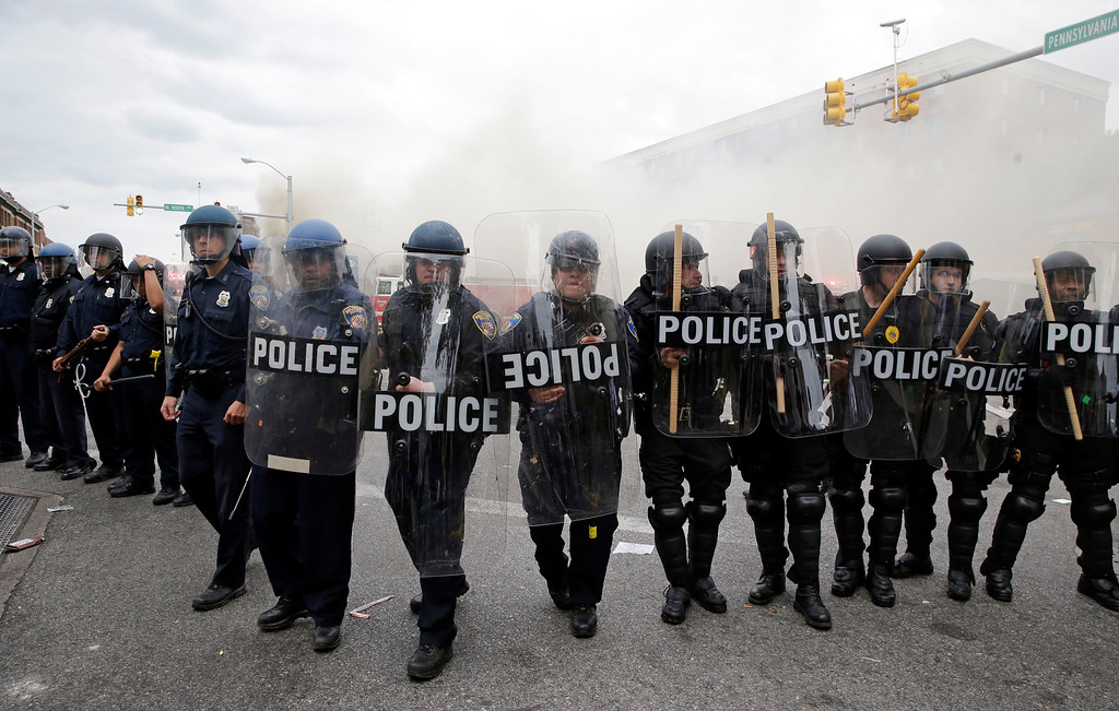 . Police advance toward protestors as a store burns, Monday, April 27, 2015, during unrest following the funeral of Freddie Gray in Baltimore. Gray died from spinal injuries about a week after he was arrested and transported in a Baltimore Police Department van. (AP Photo/Patrick Semansky)