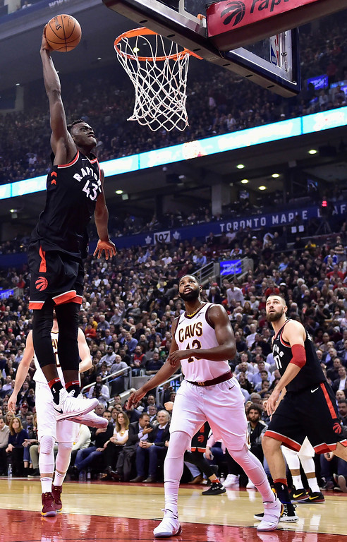. Toronto Raptors forward Pascal Siakam (43) goes up for a dunk against Cleveland Cavaliers center Tristan Thompson (13) as Raptors center Jonas Valanciunas (17) watches during the first half of an NBA basketball game Thursday, Jan. 11, 2018, in Toronto. (Frank Gunn/The Canadian Press via AP)