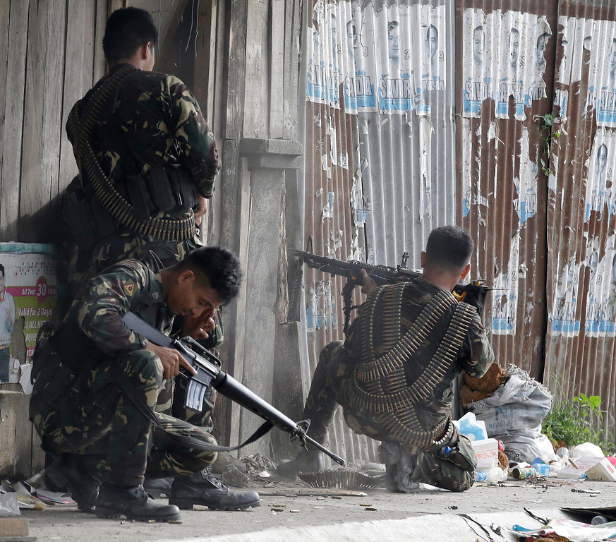 . Government troopers fire their weapons as they continue their assault at Muslim rebels Thursday, Sept. 12, 2013 in Zamboanga city in southern Philippines.  (AP Photo/Bullit Marquez)
