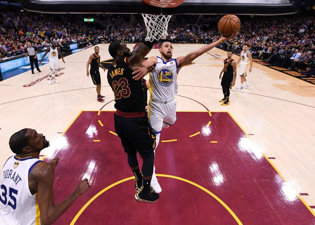 . Golden State Warriors guard Stephen Curry (30 shoots around Cleveland Cavaliers forward LeBron James (23) in Game 4 of basketball\'s NBA Finals on Friday, June 8, 2018, in Cleveland. The Warriors defeated the Cavaliers 108-85 to sweep the series. (Gregory Shamus/Pool Photo via AP)