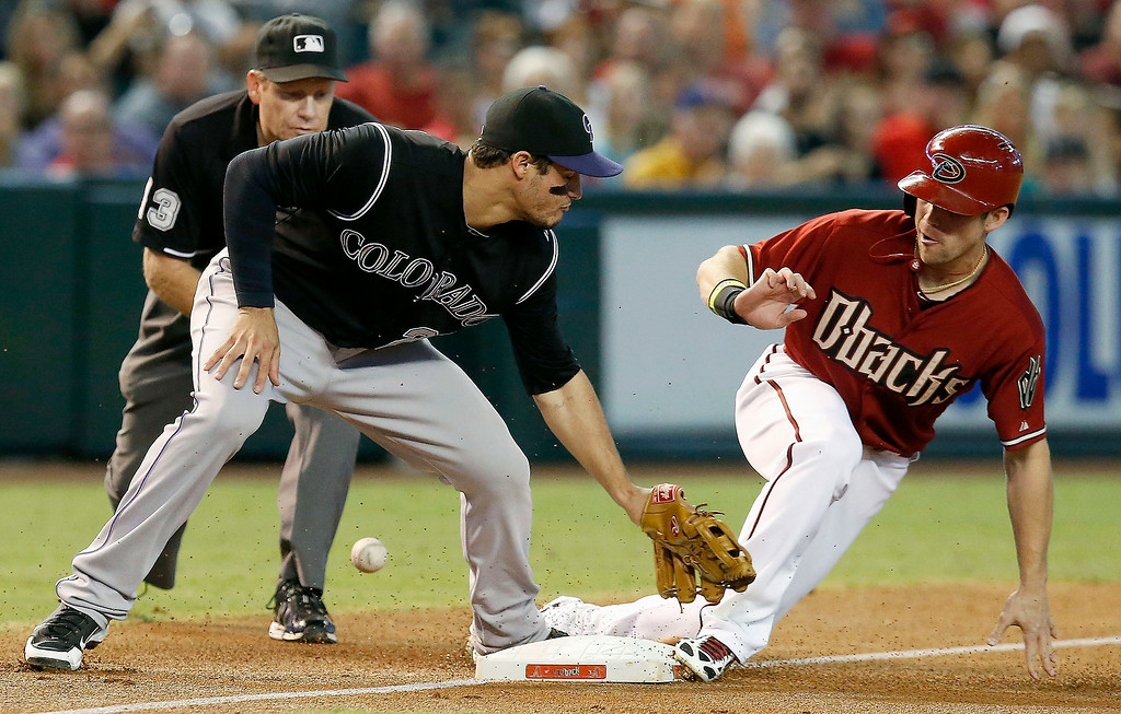 . Arizona Diamondbacks\' Ender Inciarte, right, slides safely into third base after stealing second and advancing to third on a wild pitch as Colorado Rockies\' Nolan Arenado, left, is unable to catch the ball thrown by the catcher during the first inning of a baseball game Sunday, Aug. 31, 2014, in Phoenix. (AP Photo/Ross D. Franklin)