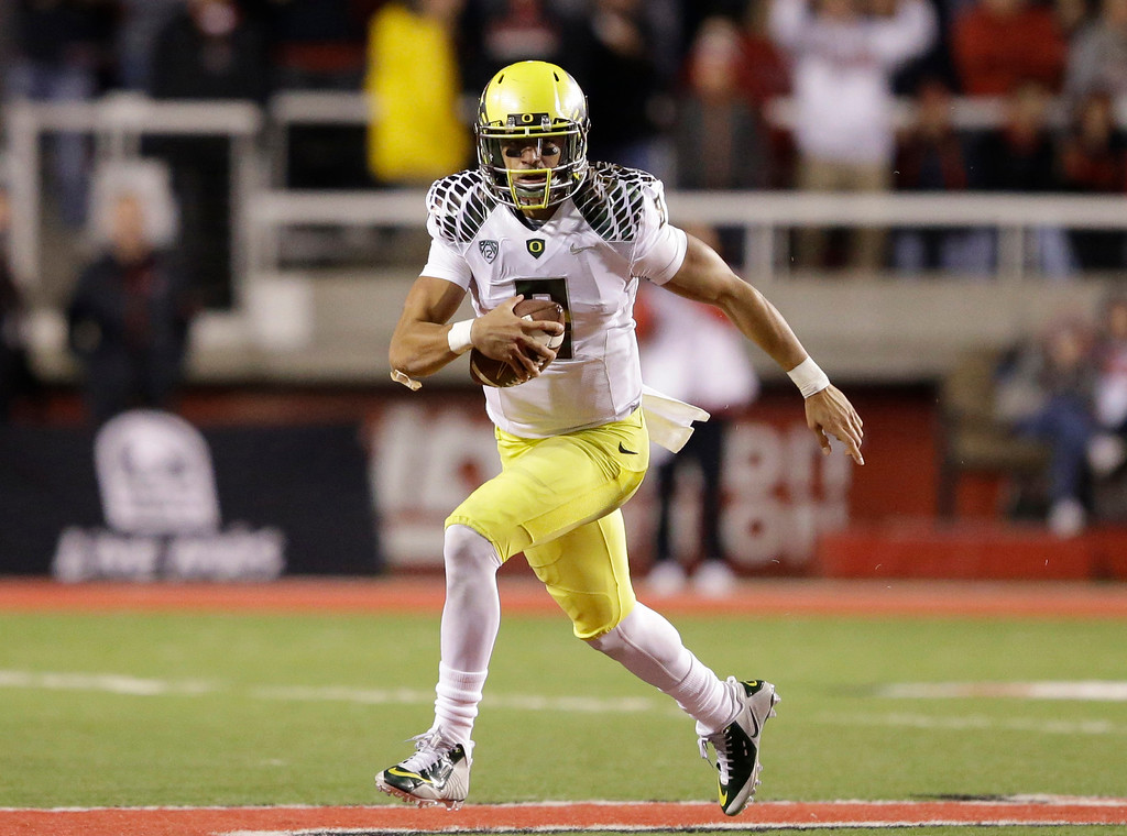 . In this Nov. 8, 2014, file photo, Oregon quarterback Marcus Mariota (8) carries the ball in the second half during an NCAA college football game against Utah in Salt Lake City. (AP Photo/Rick Bowmer, File)