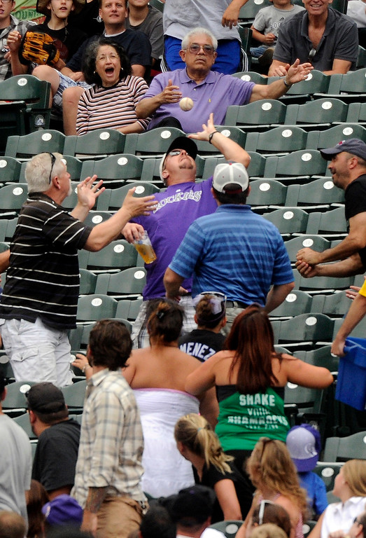 . Fans grabbed a foul ball Thursday. The Colorado Rockies hosted the Miami Marlins at Coors Field Thursday afternoon, July 25, 2013. Photo By Karl Gehring/The Denver Post