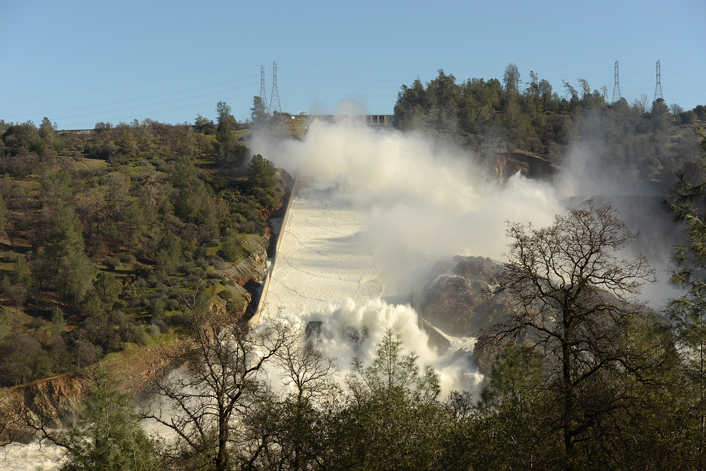 . Water flows over the emergency spillway Saturday, Feb. 11, 2017, and in the main spillway in Oroville, California. (Dan Reidel -- Enterprise-Record)