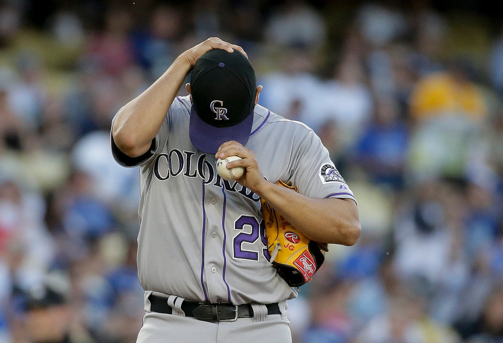 . Colorado Rockies starting pitcher Jorge De La Rosa fixes his cap after giving up a run to the Los Angeles Dodgers during first inning of a baseball game in Los Angeles, Wednesday, June 18, 2014. (AP Photo/Chris Carlson)