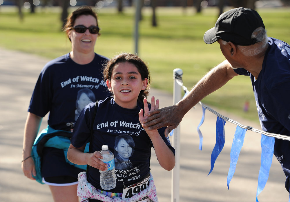. Alex Guzman, followed closely by her mother Laura, gets a high five from a volunteer as she finishes the race.  Family, colleagues, and friends of slain Denver Police Officer Celena Hollis turned out April 7, 2013 for a 5k run and walk to raise money for a scholarship fun and a memorial bench in City Park in Denver, CO.  Over 300 runners and walkers participated in the race that started at 9:00 am.  The race looped around City Park.  After the race, a gathering was held to remember Hollis and 22 white doves were released in her memory.  (Photo By Helen H. Richardson/ The Denver Post)