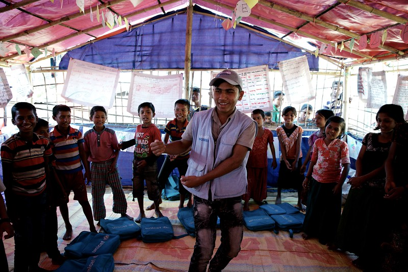 0137-0138Mohammad Rafiq teaches Rohingya children Burmese through songs and performance at a UNICEF-supported learning centre at the Balukhali makeshift settlement in Ukhia, Cox's Bazar, Bangladesh.     Photo: UNICEF / b.a.sujaN/Map