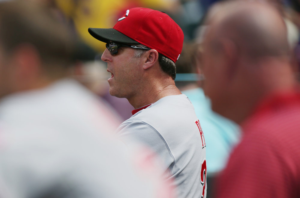 . Cincinnati Reds manager Bryan Price directs his players against the Colorado Rockies in the fourth inning of a baseball game in Denver on Sunday, Aug. 17, 2014. (AP Photo/David Zalubowski)