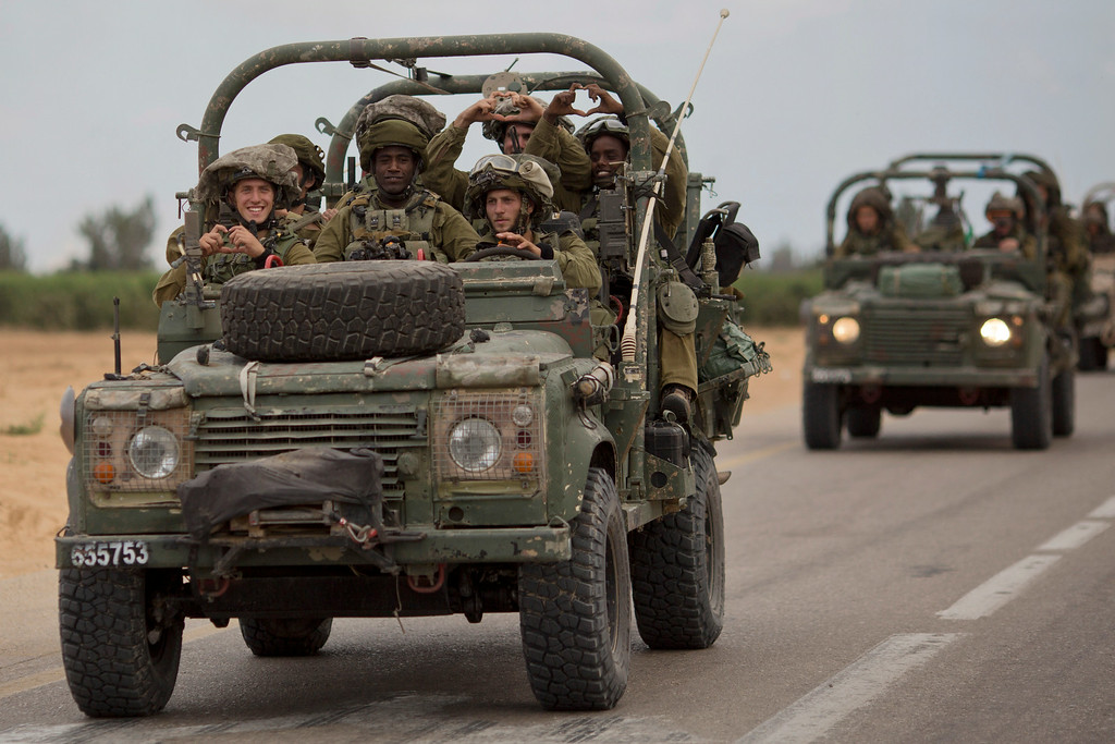 . Israeli soldiers smile as they ride on a military vehicle near the Israel-Gaza Border, Thursday, July 17, 2014. Israel and Hamas have begun observing a five-hour humanitarian cease-fire, as fighting extended into a 10th day. The two sides agreed to the pause following a request by the United Nations so that supplies could be delivered to Gaza.(AP Photo/Ariel Schalit)