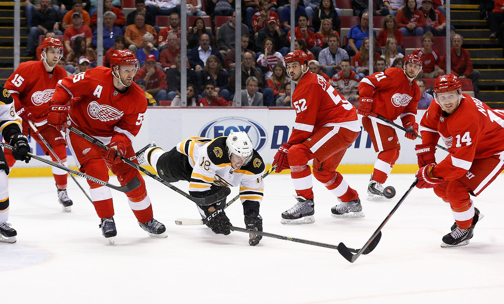 . Boston Bruins right wing Reilly Smith (18) hits the ice while attempting to attack the Detroit Red Wings defense in the third period of an NHL hockey game in Detroit, Wednesday, Oct. 15, 2014. (AP Photo/Paul Sancya)