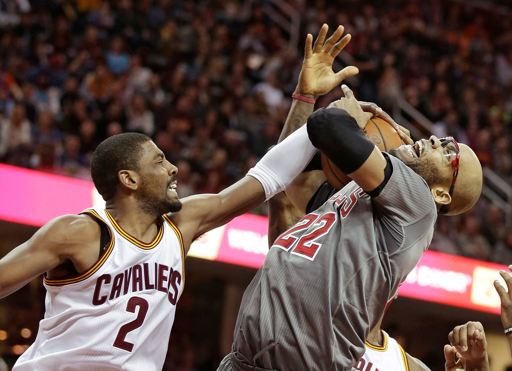 . Chicago Bulls\' Taj Gibson, right, tries to hold onto the ball against Cleveland Cavaliers\' Kyrie Irving (2) in the first half of an NBA basketball game Saturday, Jan. 23, 2016, in Cleveland. (AP Photo/Tony Dejak)