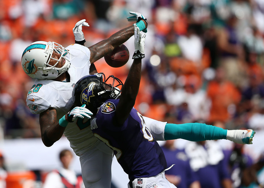 . Miami Dolphins cornerback Nolan Carroll (28), left, prevents a reception by Baltimore Ravens wide receiver Deonte Thompson (83) during the first half of an NFL football game, Sunday, Oct. 6, 2013, in Miami Gardens, Fla. (AP Photo/J Pat Carter)