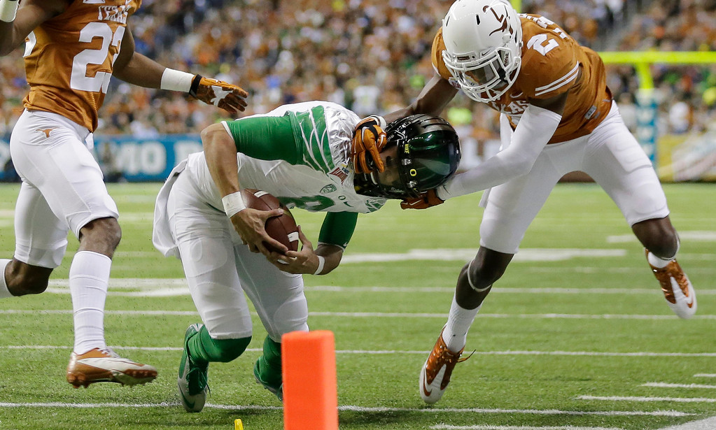 . Oregon\'s Marcus Mariota (8) is pulled down by his helmet by Texas\' Mykkele Thompson (2) during the first quarter in the Valero Alamo Bowl NCAA college football game, Monday,  Dec. 30, 2013, in San Antonio. (AP Photo/Eric Gay)