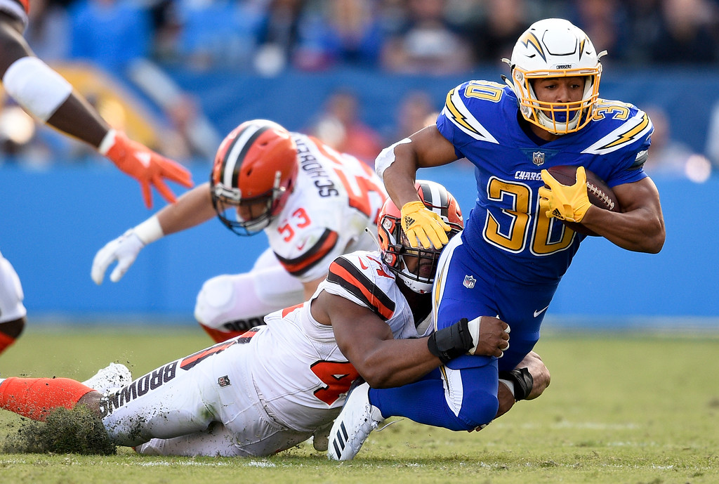 . Los Angeles Chargers running back Austin Ekeler, right, is tackled by Cleveland Browns defensive end Nate Orchard during the first half of an NFL football game Sunday, Dec. 3, 2017, in Carson, Calif. (AP Photo/Kelvin Kuo)
