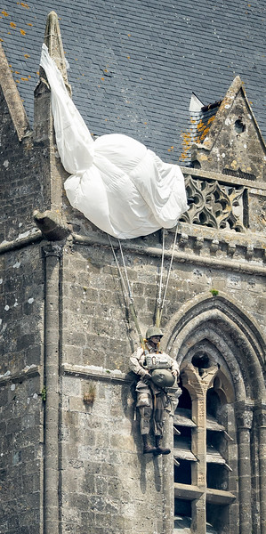 A memorial effigy of Pvt John Steele hangs from the tower