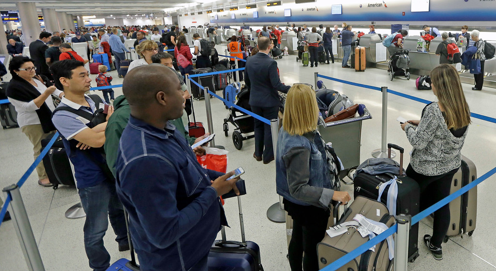 . Passengers stand in line to check in their luggage at Miami International Airport, Wednesday, Nov. 23, 2016, in Miami. Almost 49 million people are expected to travel 50 miles or more for the Thanksgiving holiday, the most since 2007, according to AAA.  (AP Photo/Alan Diaz)