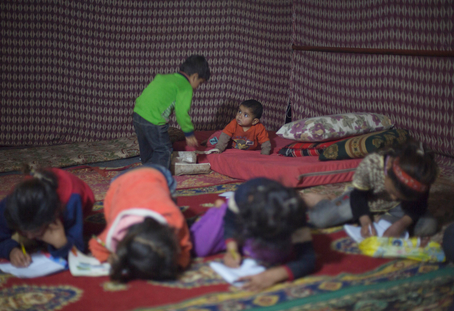 . In this Wednesday, April 9, 2014 photo, a Syrian boy plays with his brother as girls study inside a tent in an unofficial refugee camp on the outskirts of Amman, Jordan. Some Syrians have set up informal camps to flee the tensions at Zaatari, the region\'s largest camp for Syrian refugees, and to be closer to job opportunities. (AP Photo/Khalil Hamra)