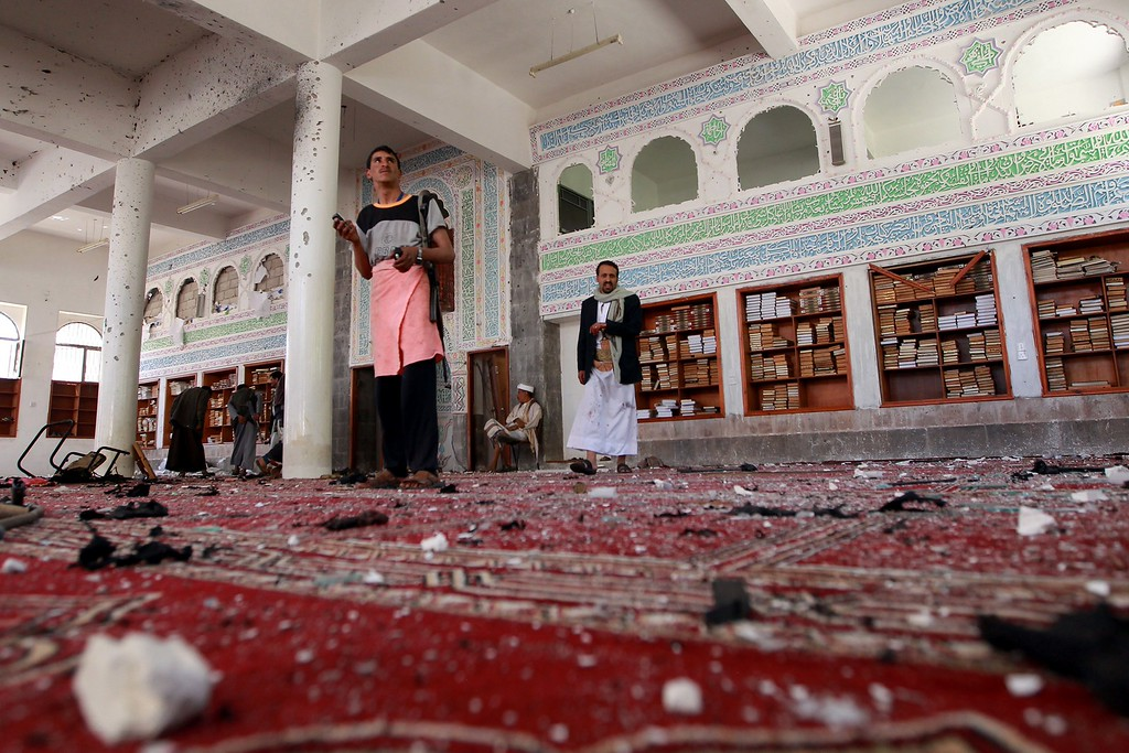 . Yemeni armed men inspect the damage following a bomb explosion at the Badr mosque in southern Sanaa on March 20, 2015. Triple suicide bombings killed at least 55 people at mosques in the Yemeni capital attended by Shiite Huthi militiamen who have seized control of the city. AFP PHOTO / MOHAMMED HUWAIS/AFP/Getty Images