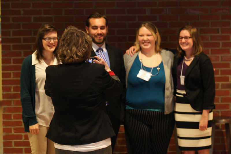 Mentor, Dr. LaShea Stuart takes a photo of her Literature presenters, (left to right) Brittney Clark, George Millar, Molly Law, and Allison Parrish.