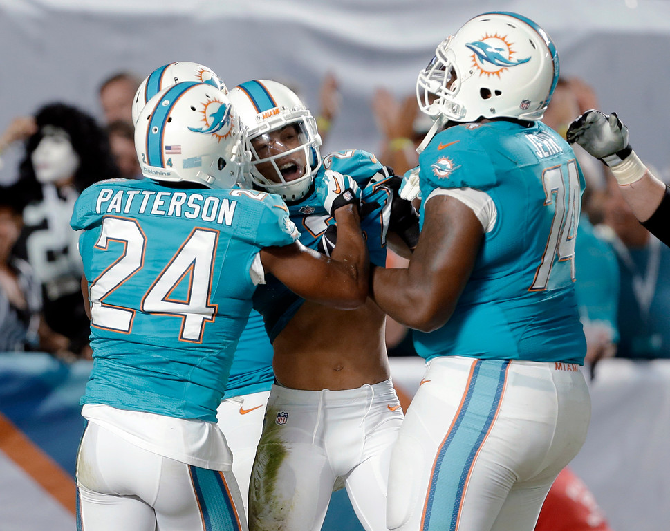 . Miami Dolphins cornerback Brent Grimes, center, is congratulated by cornerback Dimitri Patterson (24), guard John Jerry (74) and another teammate after Grimes intercepted a pass by Cincinnati Bengals quarterback Andy Dalton and returned it for a touchdown, during the second half of an NFL football game, Thursday, Oct. 31, 2013, in Miami Gardens, Fla. (AP Photo/Lynne Sladky)