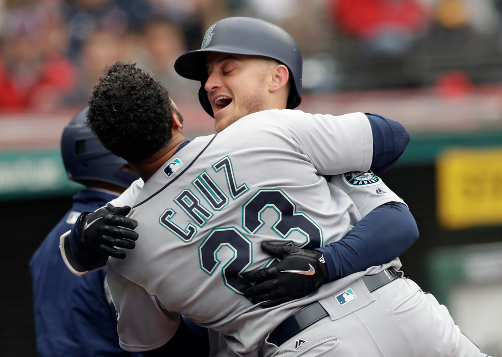. Seattle Mariners\' Kyle Seager, right, hugs Nelson Cruz after Seager hit a two-run home run off Cleveland Indians relief pitcher Zach McAllister in the fourth inning of a baseball game, Saturday, April 28, 2018, in Cleveland. Robinson Cano scored on the play. (AP Photo/Tony Dejak)