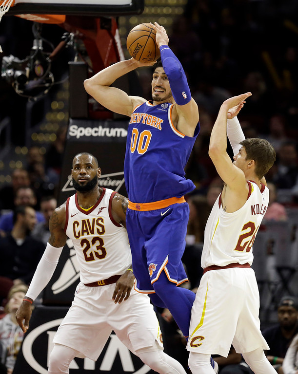 . New York Knicks\' Enes Kanter (00) passes between Cleveland Cavaliers\' LeBron James (23) and Kyle Korver (26) in the first half of an NBA basketball game, Sunday, Oct. 29, 2017, in Cleveland. (AP Photo/Tony Dejak)