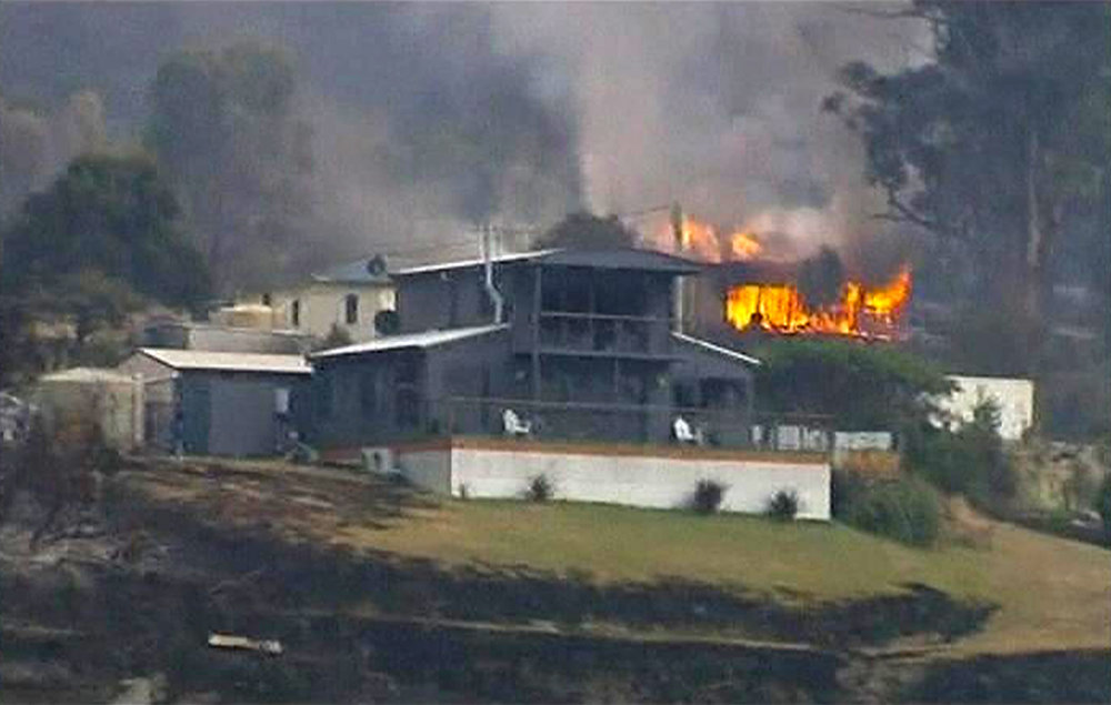 . A house is seen on fire in the Tasmanian town of Dunalley, in this still image taken from video shot January 5, 2013. Bush fires in the Tasmanian town of Dunalley have destroyed up to 80 homes, and at least one person is feared dead. Hundreds have now left the area as the fires continue to spread on the east of the Australian island state.   REUTERS/Australian Broadcasting Corporation via REUTERS TV
