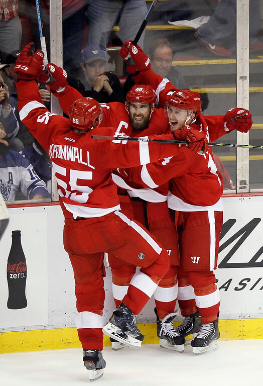 . Detroit Red Wings\' Henrik Zetterberg, center, celebrates with teammates Niklas Kronwall (55) and Gustav Nyquist, right, all of Sweden, after his overtime goal that defeated the Toronto Maples Leafs 1-0 during an NHL hockey game Saturday, Oct. 18, 2014, in Detroit. (AP Photo/Duane Burleson)