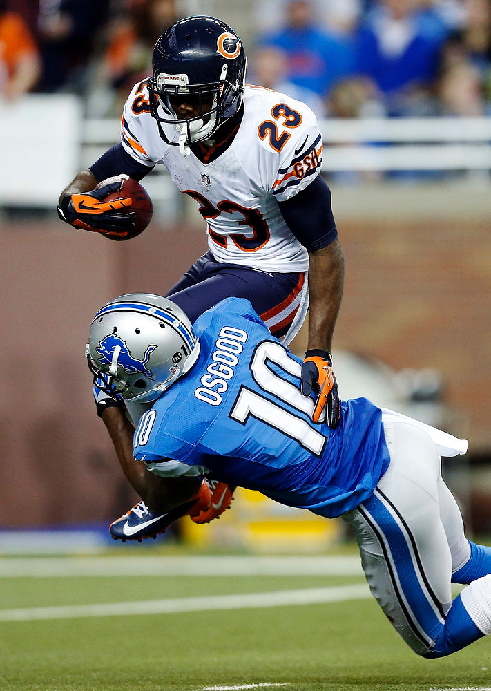 . Chicago Bears\' Devin Hester (23) is stopped by Detroit Lions\' Kassim Osgood (10) during a kick return in the third quarter of an NFL football game at Ford Field in Detroit, Sunday, Dec. 30, 2012. (AP Photo/Rick Osentoski)