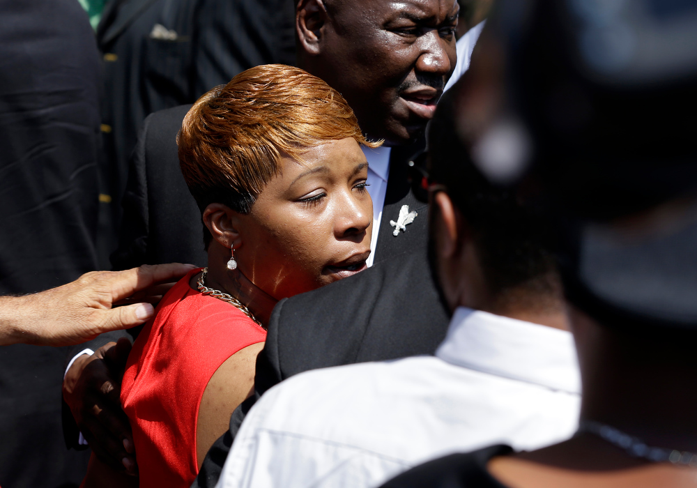 Description of . Lesley McSpadden, mother of Michael Brown, is escorted to the hearse, as people gather outside of Friendly Temple Missionary Baptist Church during the funeral for Michael Brown Monday, Aug. 25, 2014, in St. Louis. Brown, a black 18-year-old who was unarmed, he was shot Aug. 9 by Officer Darren Wilson, who is white. A grand jury is considering evidence in the case and a federal investigation is also underway. (AP Photo/Jeff Roberson)