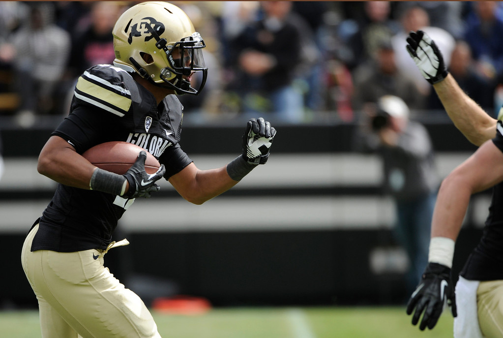 . BOULDER, CO.- APRIL13: Marques Mosley holds on tight and moves down field. The University of Colorado football team hosts its spring football game at Folsom Field under the direction of new head coach Mike MacIntyre. (Photo By Kathryn Scott Osler/The Denver Post)