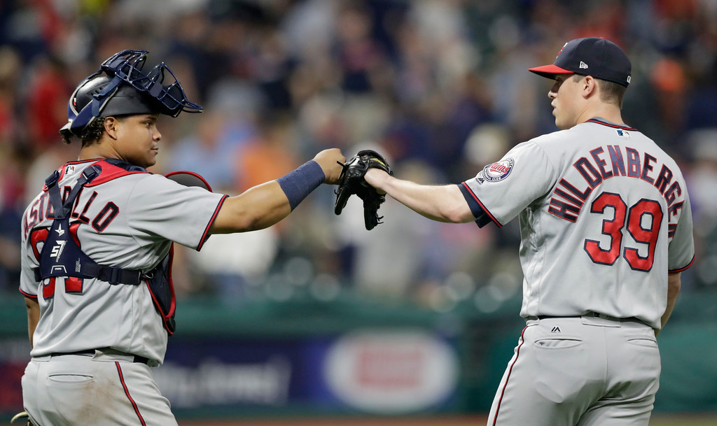 . Minnesota Twins relief pitcher Trevor Hildenberger, right, and catcher Williams Astudillo celebrate after the Twins defeated the Cleveland Indians 4-3 in a baseball game, Wednesday, Aug. 29, 2018, in Cleveland. (AP Photo/Tony Dejak)