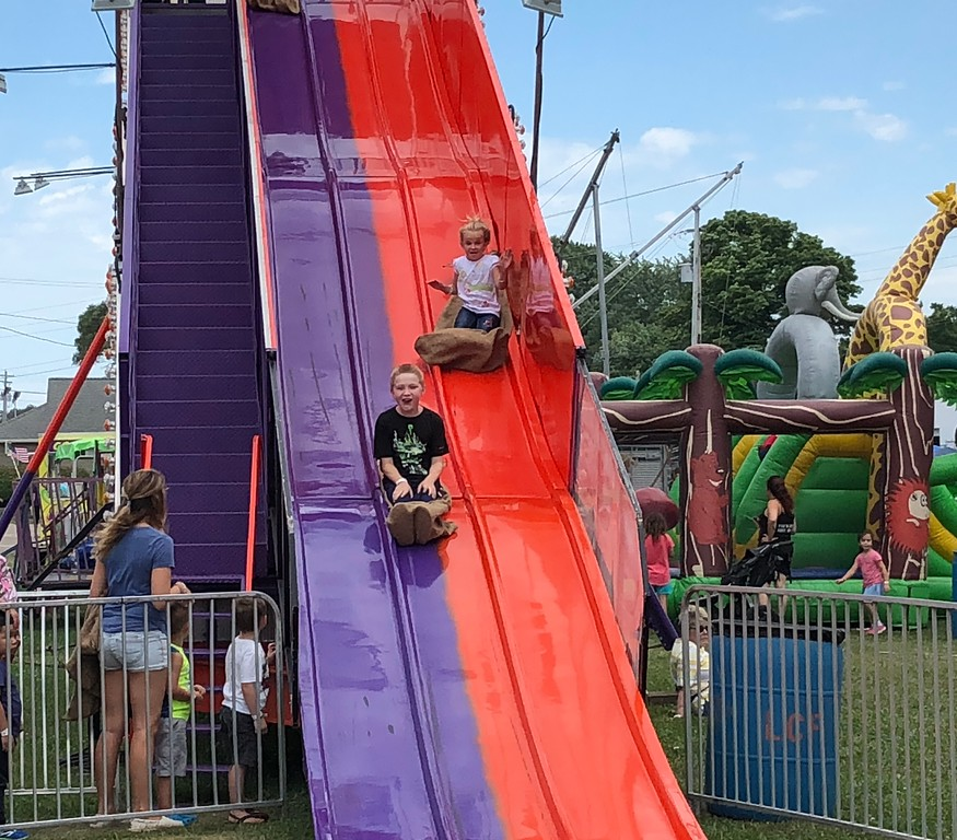 . Tawana Roberts � The News-Herald <br> Layla Williams, 7, and James Cook, 11, enjoy riding a giant slide at the 2018 Lake County Fair on July 26.