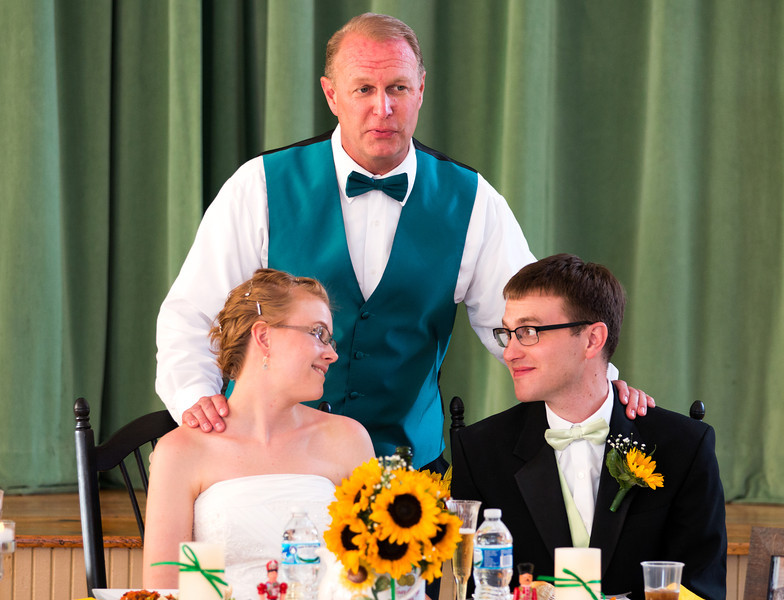 Father of the groom with bride and groom at table.jpg