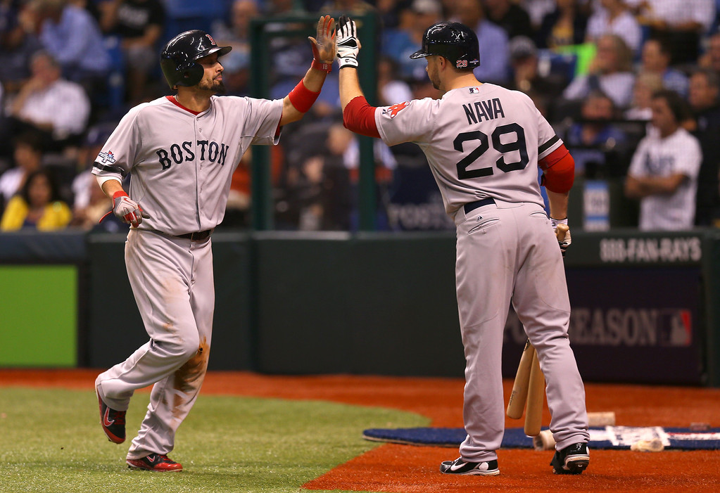 . Shane Victorino #18 of the Boston Red Sox celebrates with Daniel Nava #29 after scoring on a single by David Ortiz #34 in the fifth inning against the Tampa Bay Rays during Game Three of the American League Division Series at Tropicana Field on October 7, 2013 in St Petersburg, Florida.  (Photo by Mike Ehrmann/Getty Images)