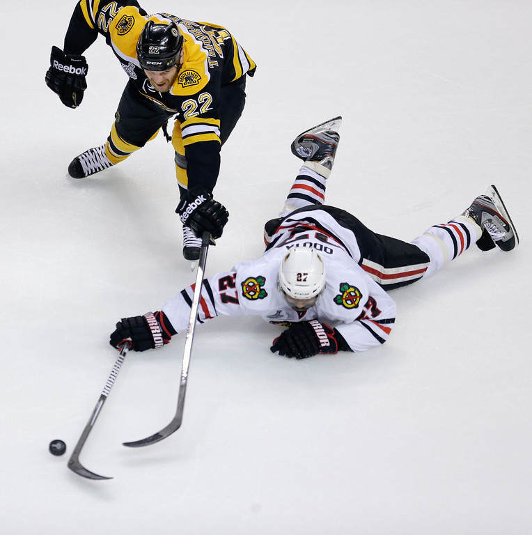 . Boston Bruins right wing Shawn Thornton (22) and Chicago Blackhawks defenseman Johnny Oduya (27), of Sweden, scrap for the puck during the first period in Game 6 of the NHL hockey Stanley Cup Finals, Monday, June 24, 2013, in Boston. (AP Photo/Charles Krupa)