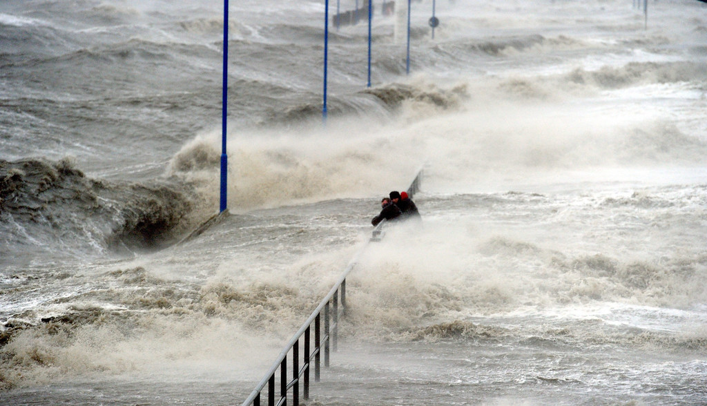 . Men hold onto a handrail as waves lash the ferry pier on the North Sea coast in Dagebuell,Germany, 05 December 2013. Storm front Xaver will reach full force later the afternoon.  EPA/CARSTEN REHDER