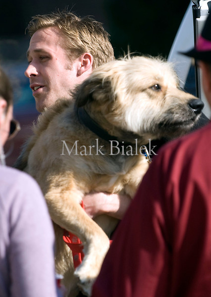 "Actor Ryan Gosling picks up his dog after a day of filming ""The Ides of March"" in downtown Ann Arbor, Michigan on March 16, 2011.  Gosling's character in the movie is Stephen Myers and the film is being directed by George Clooney."